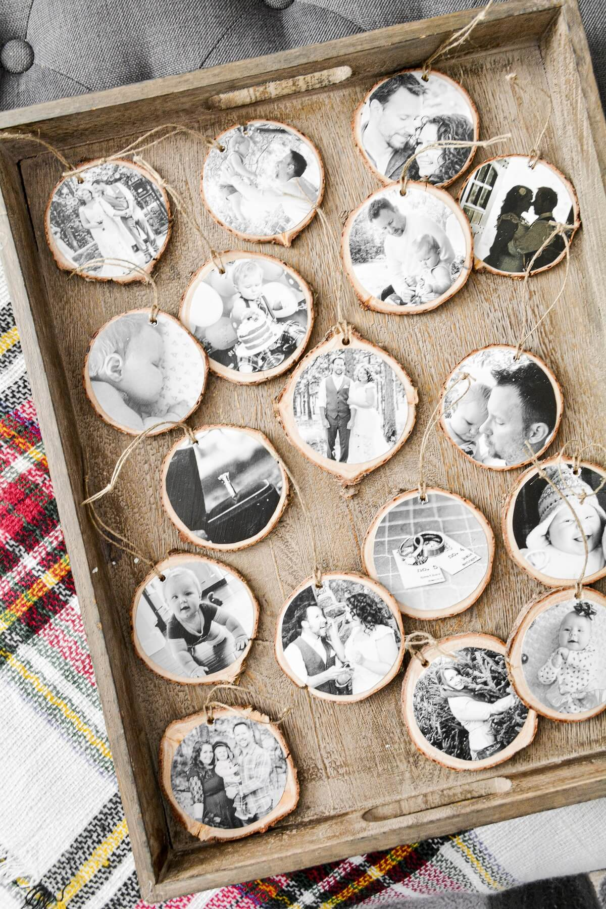 Homemade photo Christmas ornaments on a wooden tray.