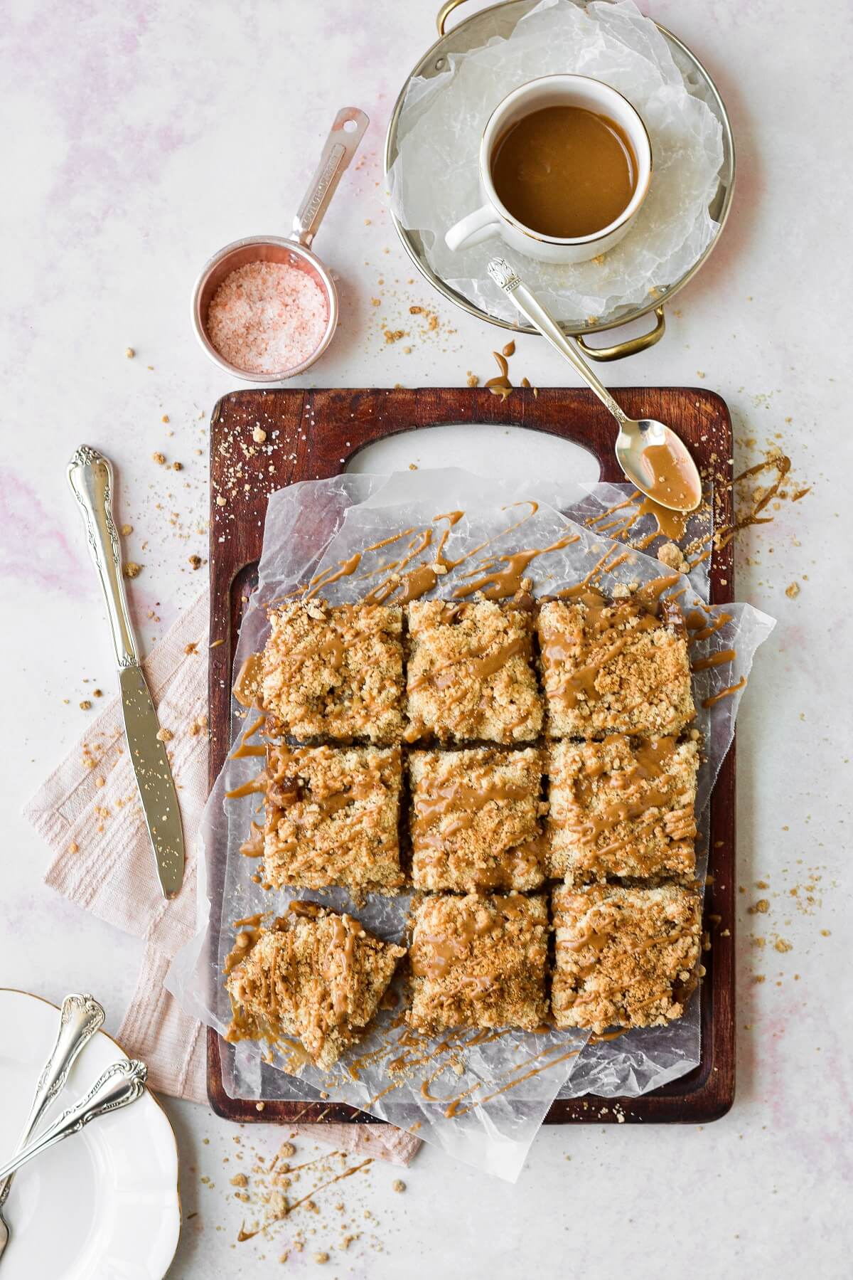 Apple crumb bars on a wooden cutting board, drizzled with maple icing.