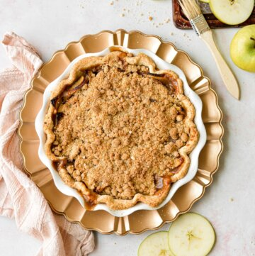 Apple crumb pie on a gold charger plate, with a pink linen napkin and apple slices scattered around.