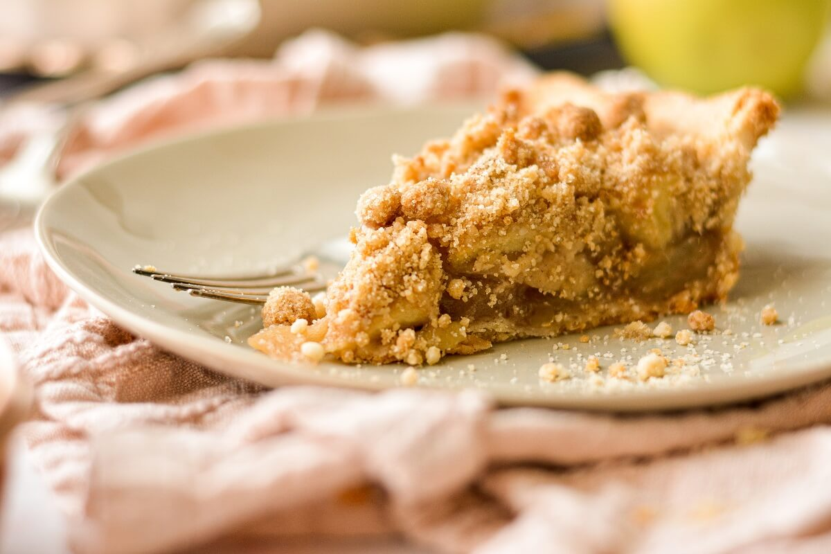 A slice of apple crumb pie on a beige plate.