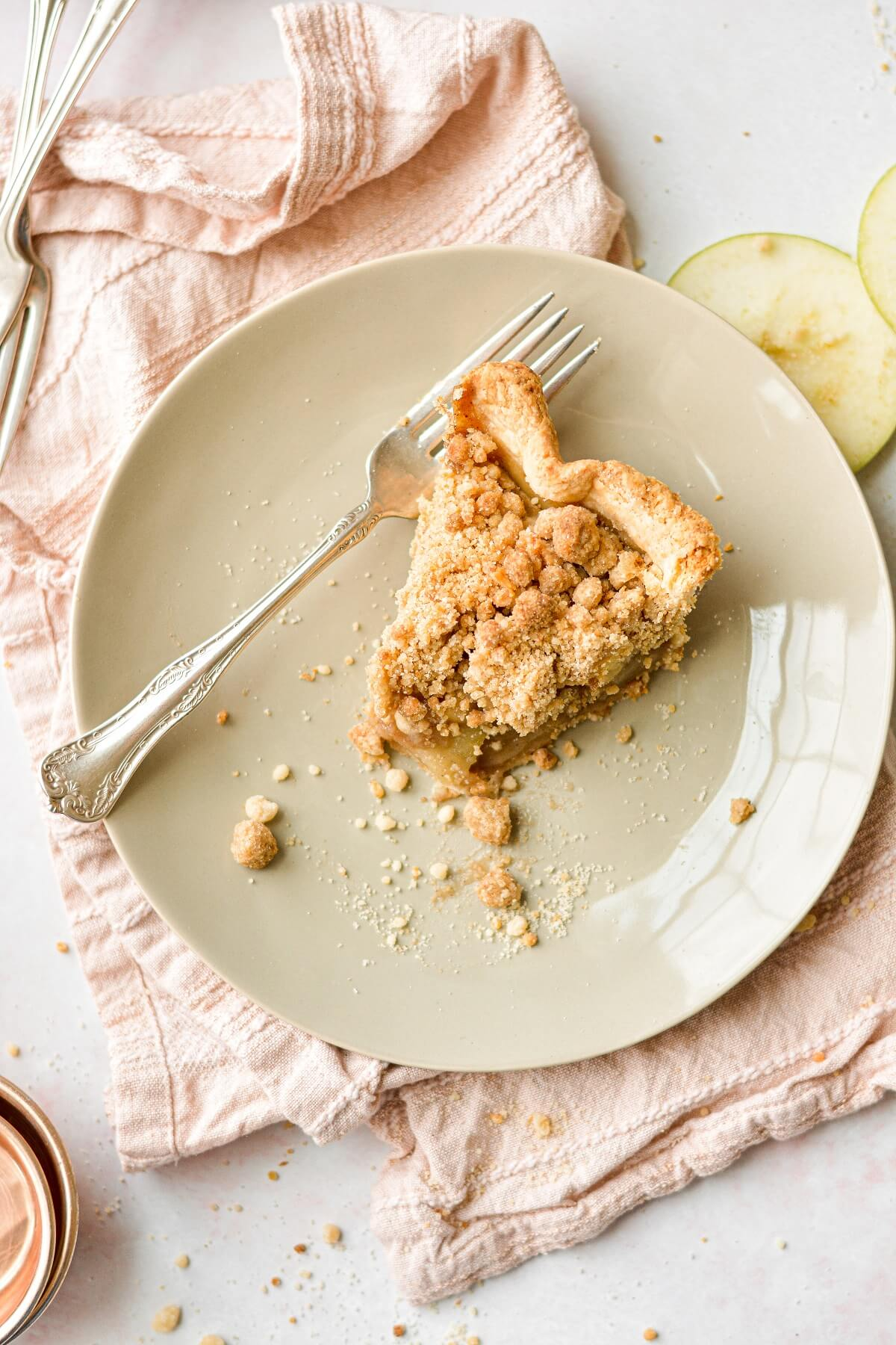 A slice of apple crumb pie on a beige plate, next to a pink linen napkin.