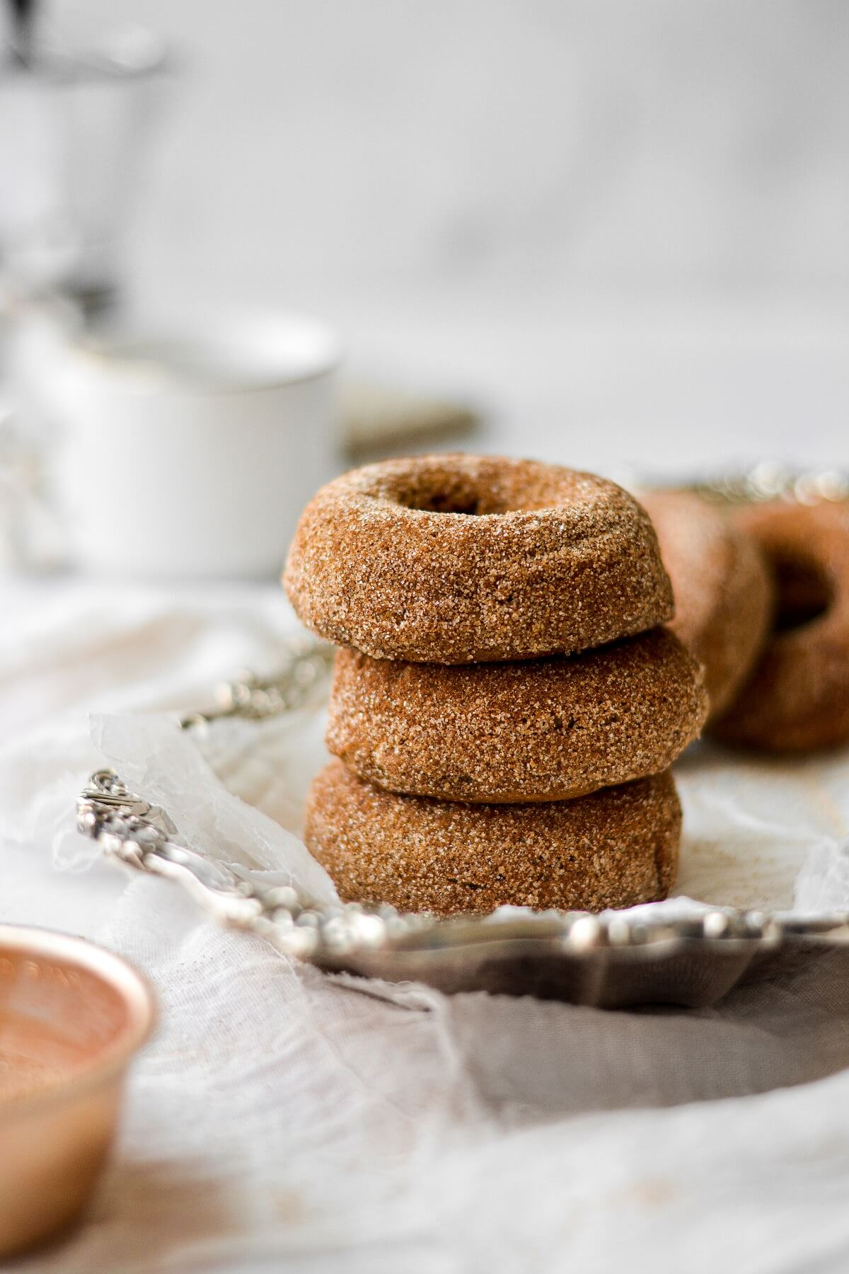 Baked pumpkin spice donuts, coated in cinnamon sugar, stacked on a silver plate.