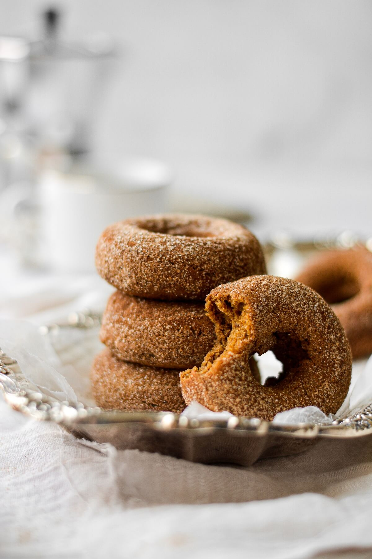 Pumpkin donuts, coated in cinnamon sugar, one with a bite taken out of it, stacked on a silver plate.