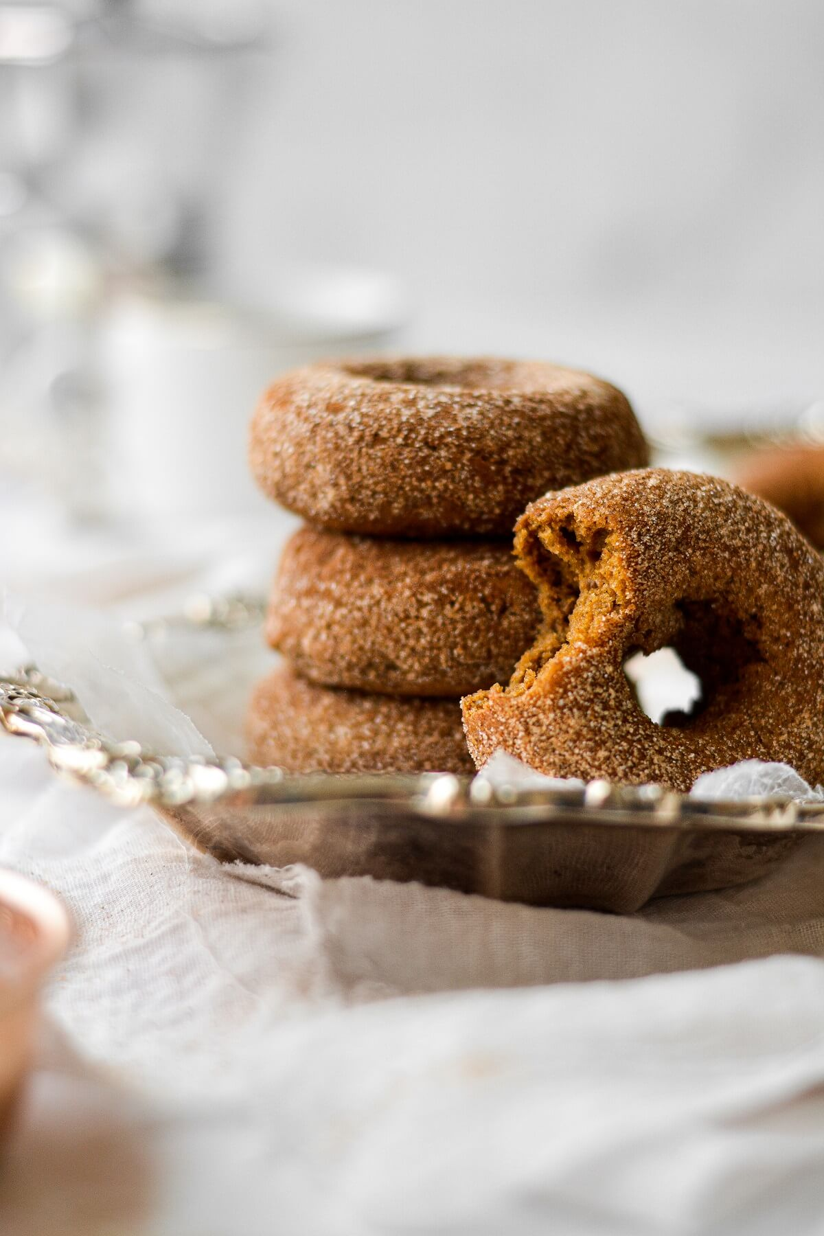 Baked pumpkin spice donuts, coated in cinnamon sugar, one with a bite taken out of it, stacked on a silver plate.