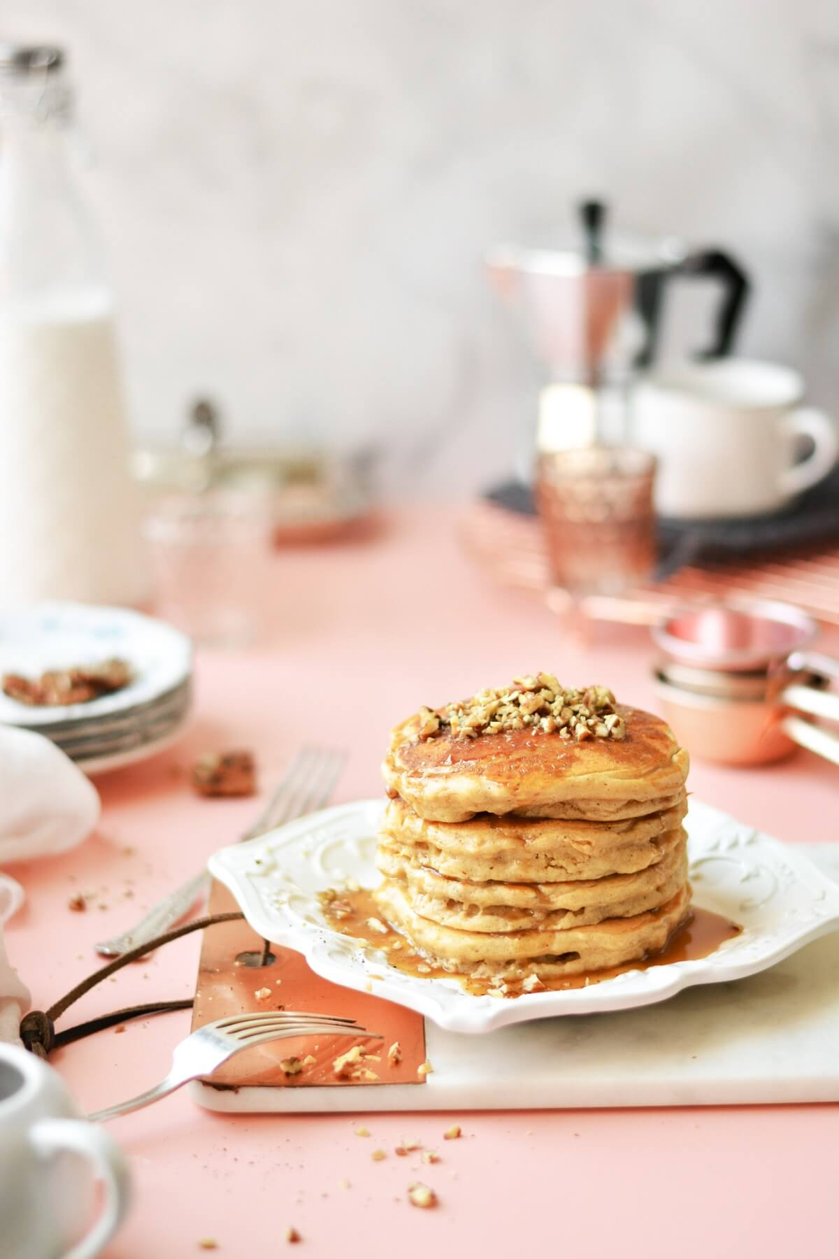 A stack of pancakes topped with pecans and toffee sauce, on a white plate, surrounded by plates and coffee cups.