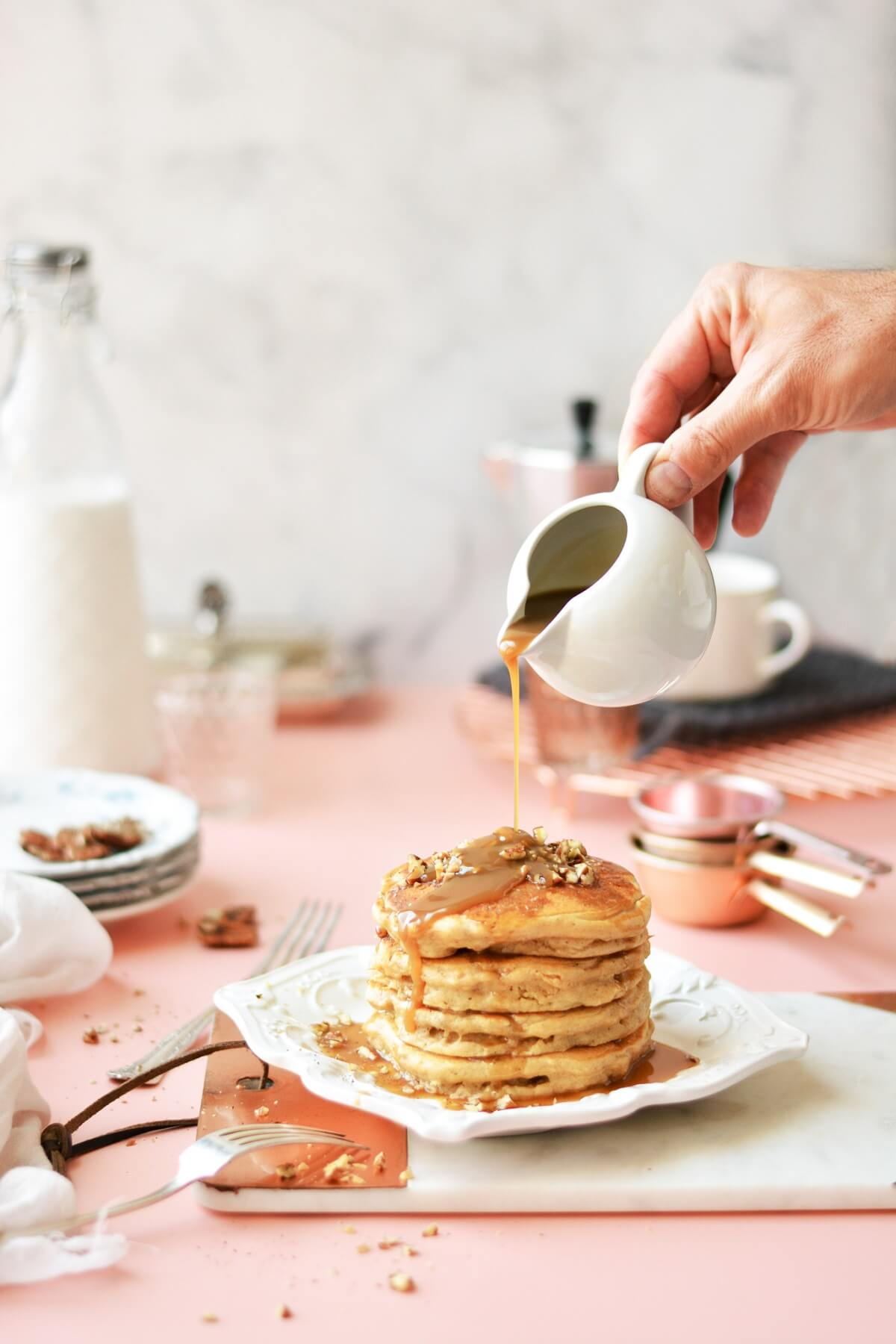 A stack of butter pecan pancakes on a white plate, with a pitcher of toffee sauce being poured onto the pancakes, all surrounded by plates and coffee cups.