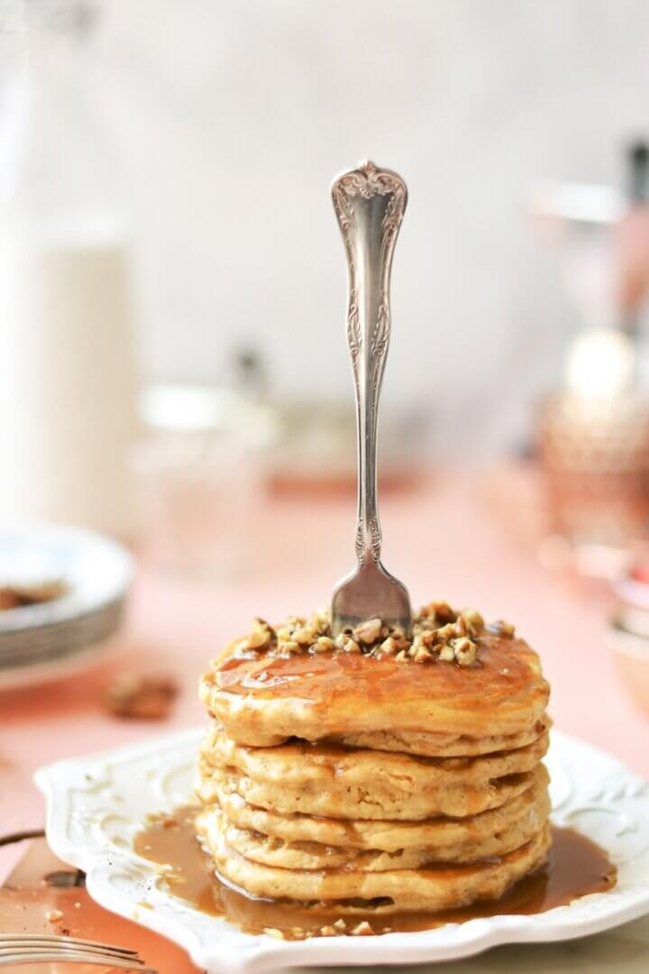A stack of pancakes, with pecans and toffee sauce, on a white plate, and a fork standing upright in the pancakes.