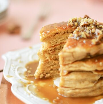 A closeup shot of butter pecan pancakes, topped with pecans and toffee sauce, and one bite cut.