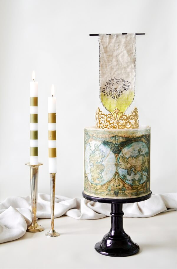 Game of Thrones Cake, on a black cake stand, topped with a gold crown and the Stark banner, with gold and white candles.
