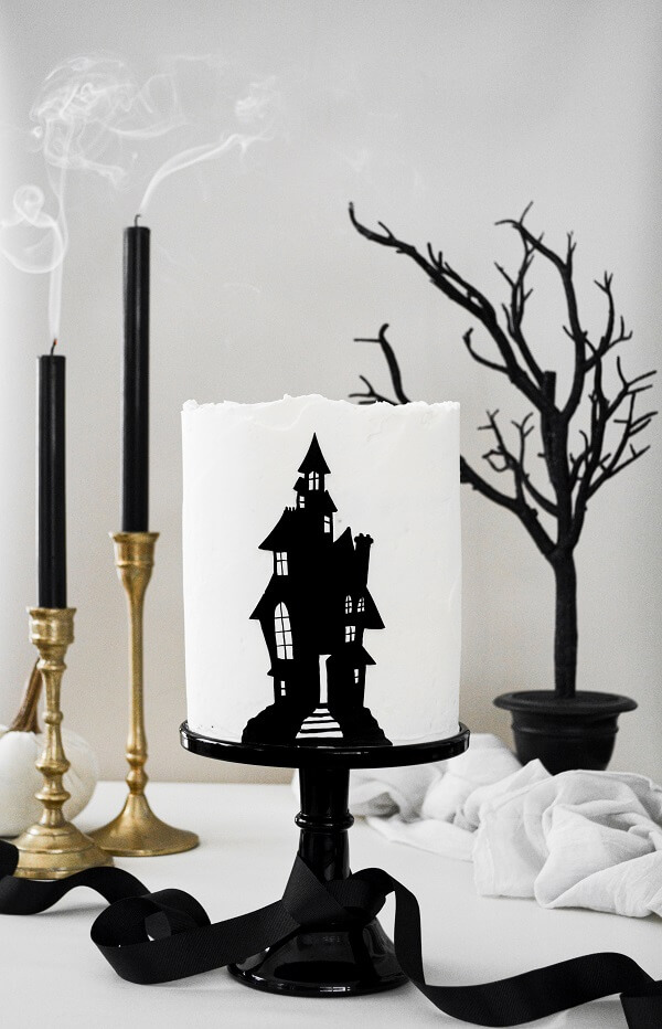 A haunted house layer cake on a black cake stand, with gold candlesticks, black candles and a black tree.