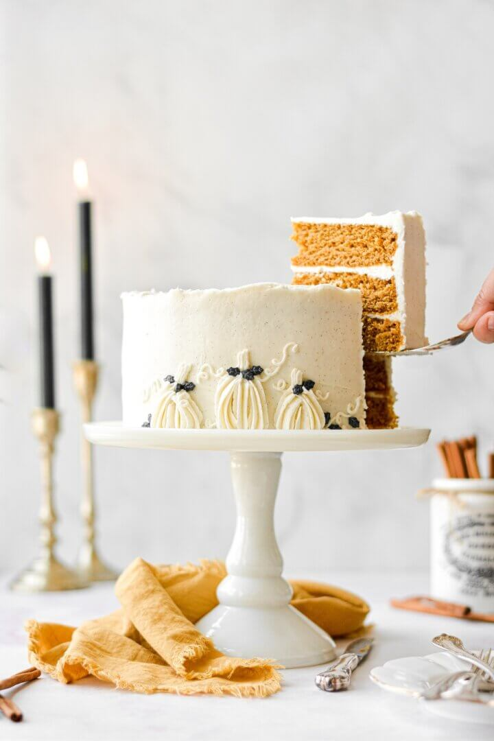 Brown butter pumpkin cake, with vanilla bean buttercream and decorated with buttercream pumpkins, sitting on a white cake stand next to a yellow linen napkin, with one slice being lifted from the cake.