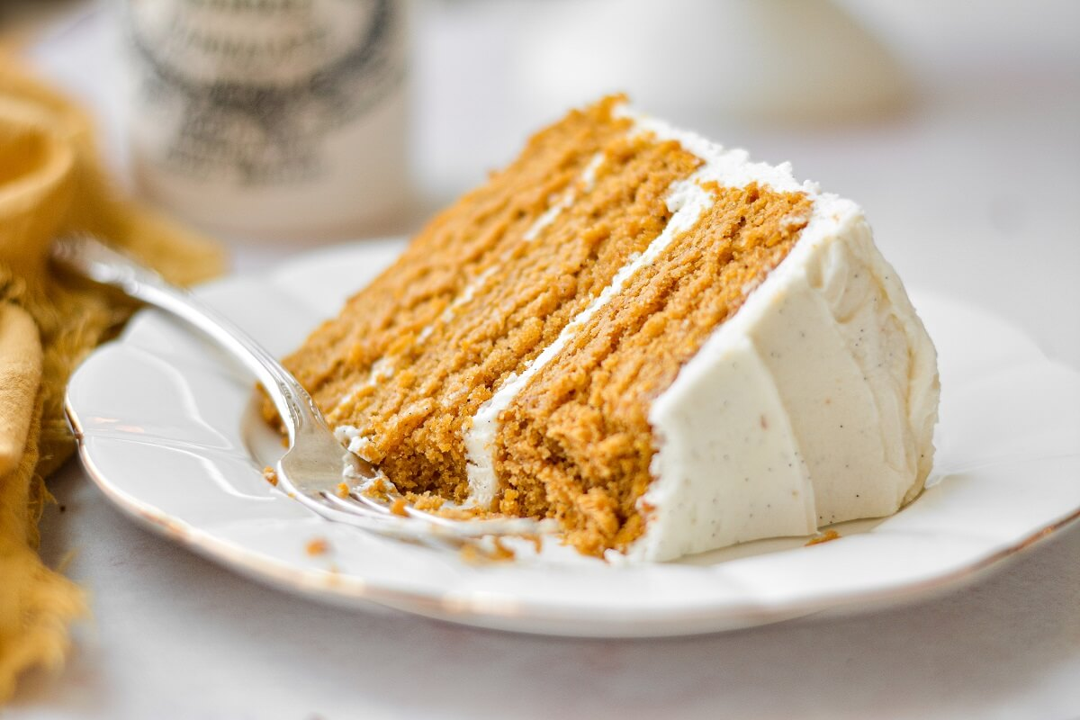 A slice of brown butter pumpkin cake on a white plate.