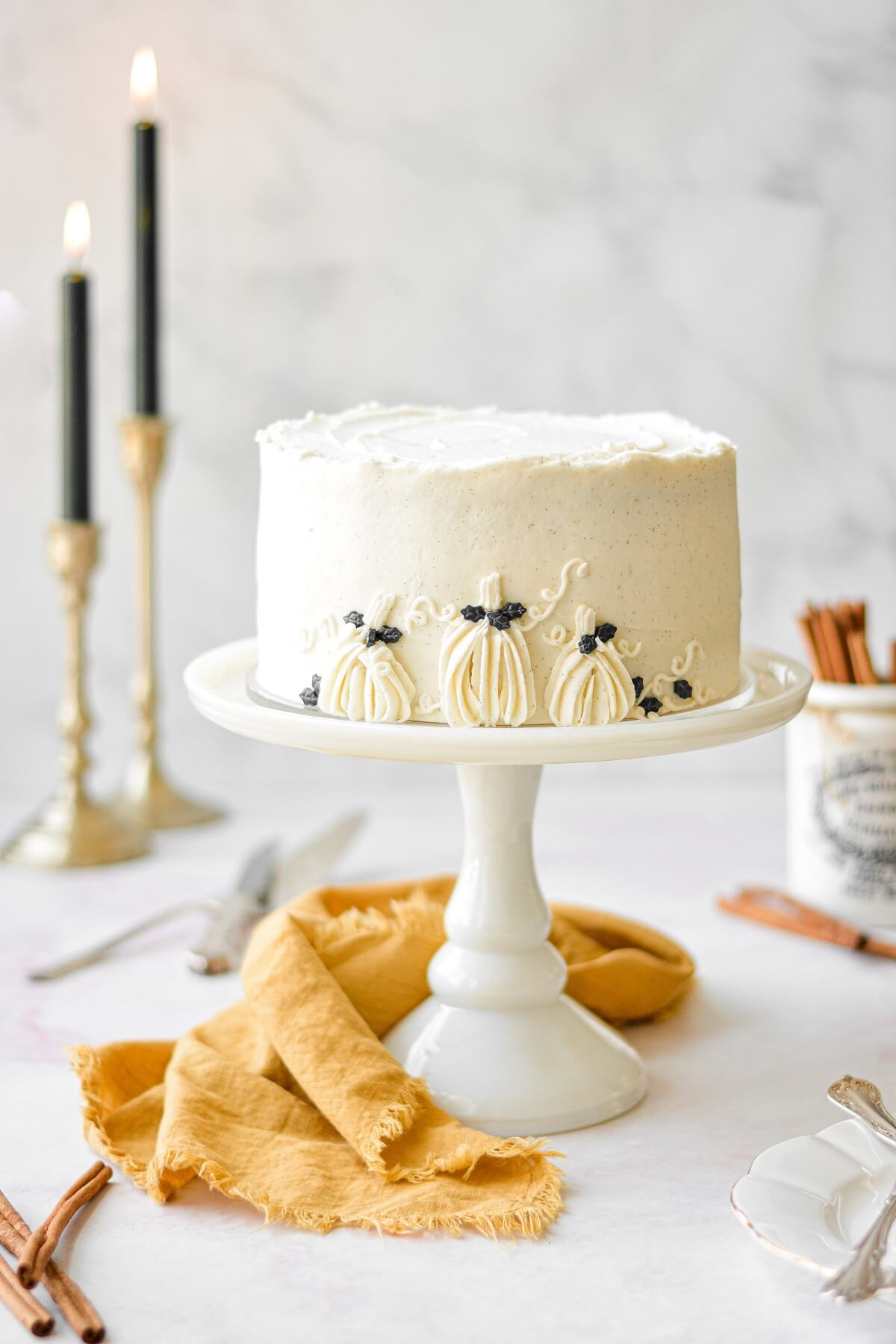Brown butter pumpkin cake, with vanilla bean buttercream and decorated with buttercream pumpkins, sitting on a white cake stand next to a yellow linen napkin.