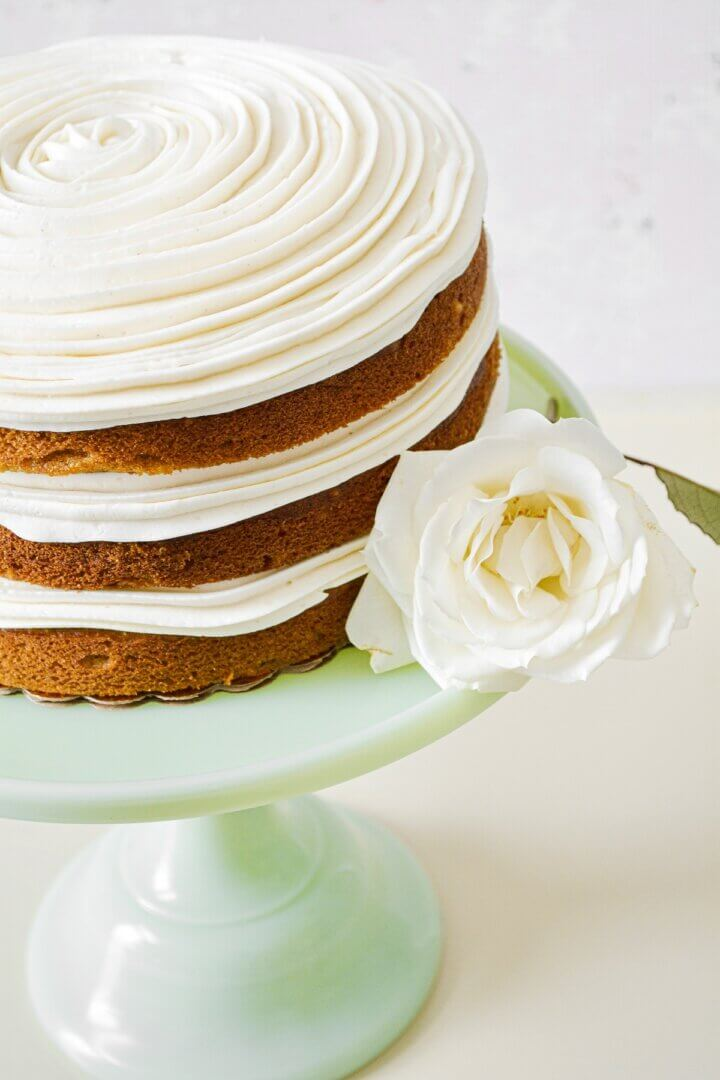 A naked, three-layer pumpkin cake, filled with swirls of buttercream, on a green cake stand.