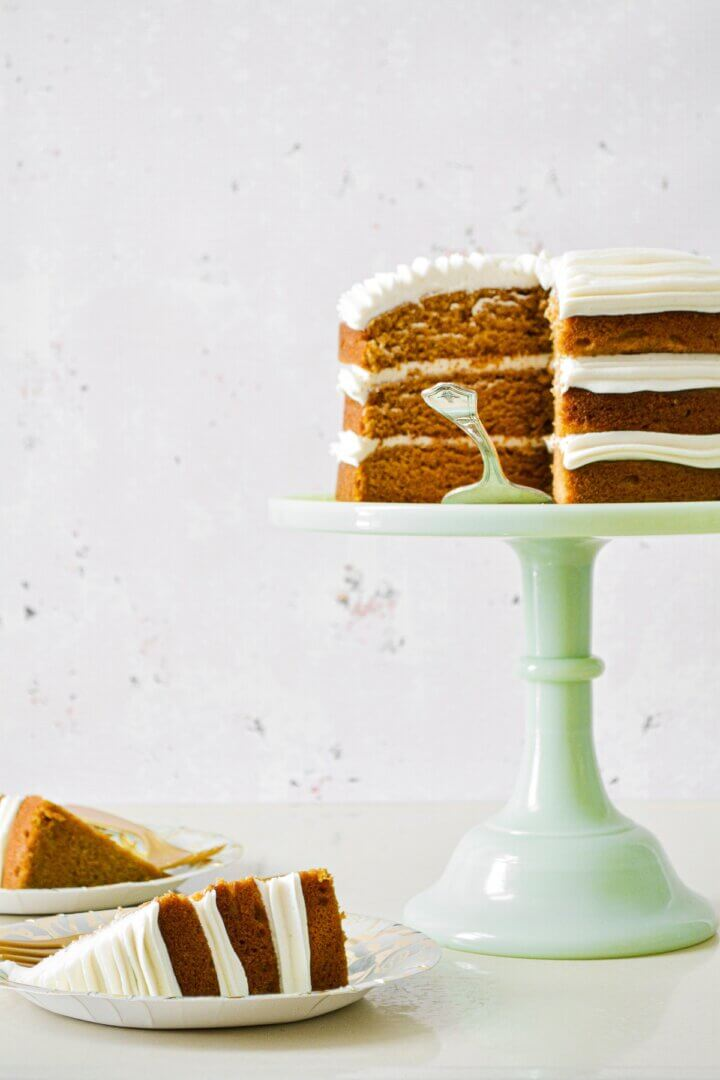 A naked, three-layer pumpkin cake, filled with swirls of buttercream, on a green cake stand, with two slices of cake on plates.