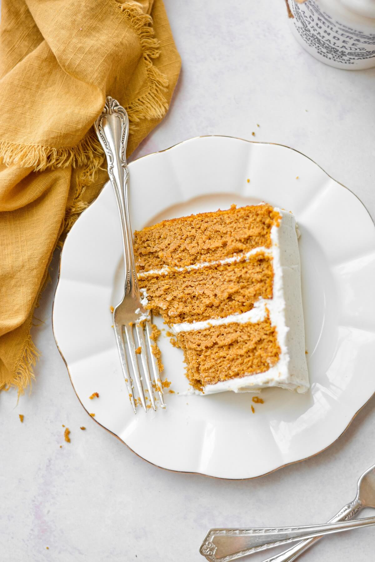 Overhead shot of a slice of pumpkin cake on a white plate, with a vintage silver fork, next to a yellow linen napkin.