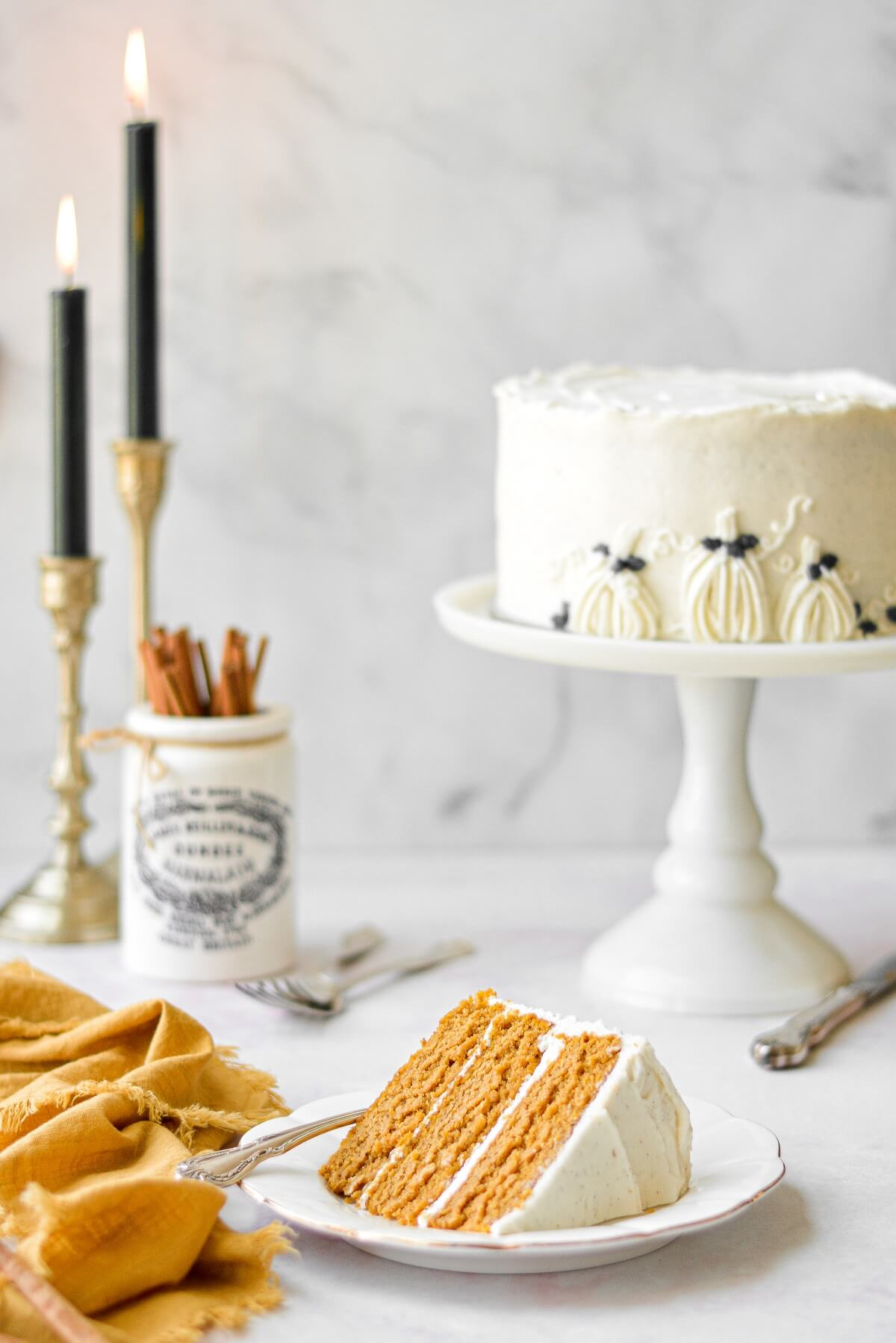 A slice of pumpkin cake on a white plate, next to a yellow linen napkin, with the cake in the background on a white cake stand.