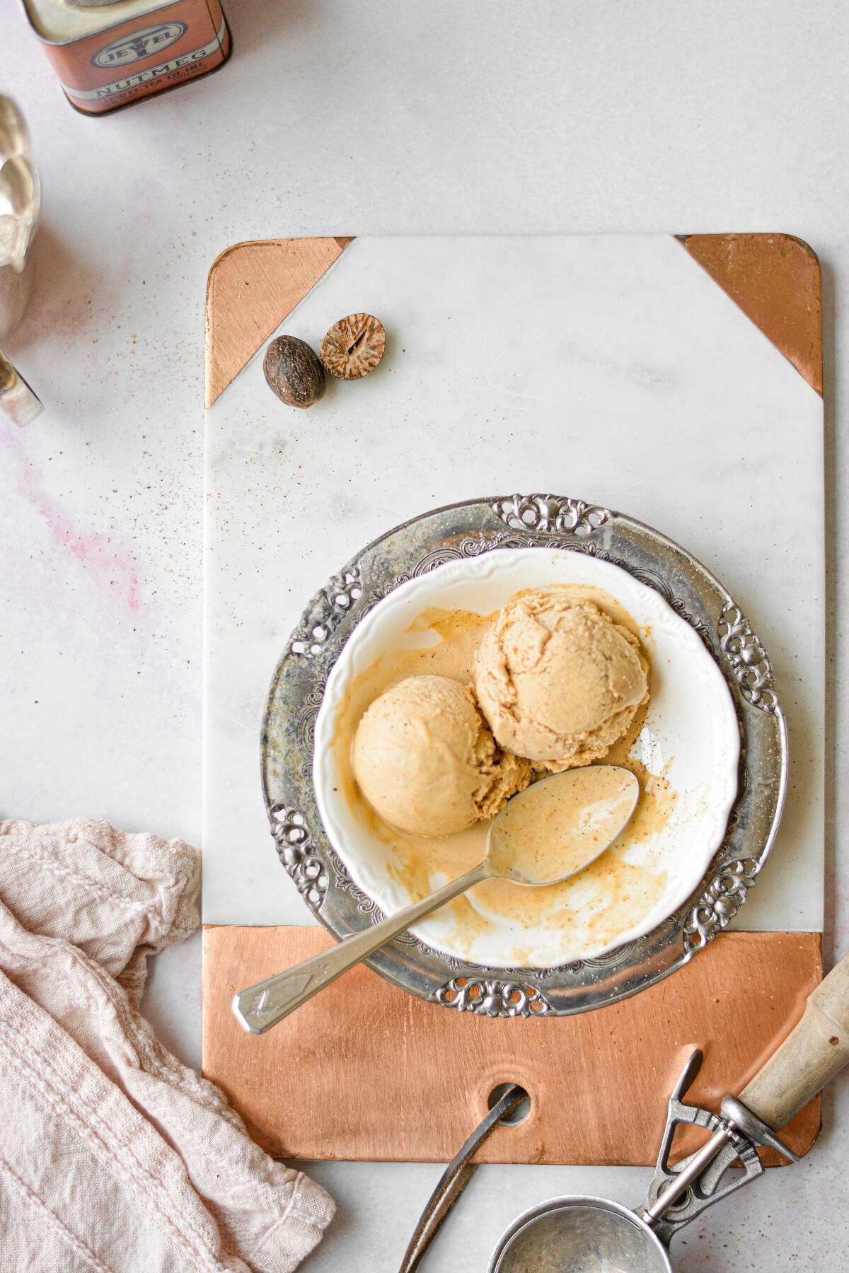 Pumpkin ice cream in a white and silver bowl, sitting on a copper and marble cutting board.