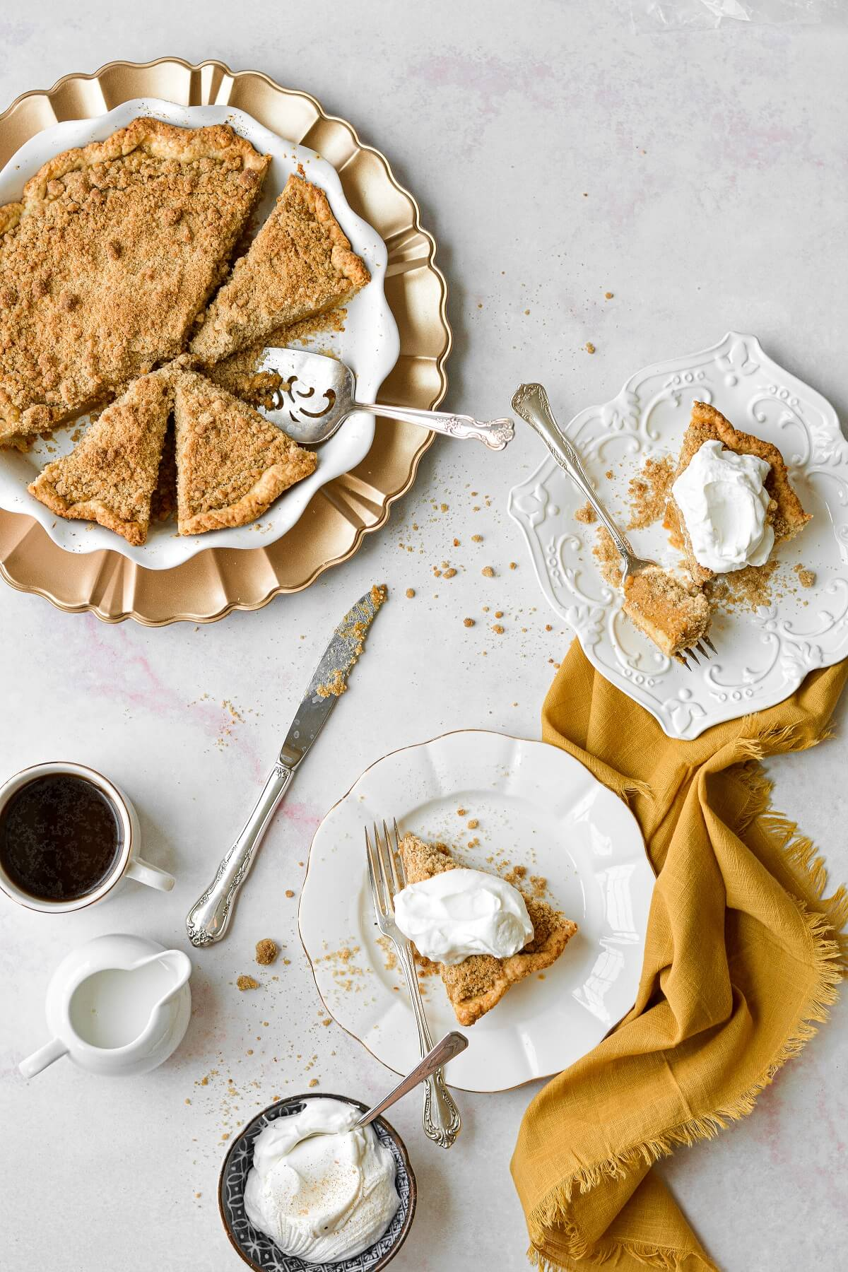 An arrangement of a pumpkin streusel pie, with several slices cut on white plates, topped with whipped cream, and surrounded by crumbs and a yellow linen napkin.