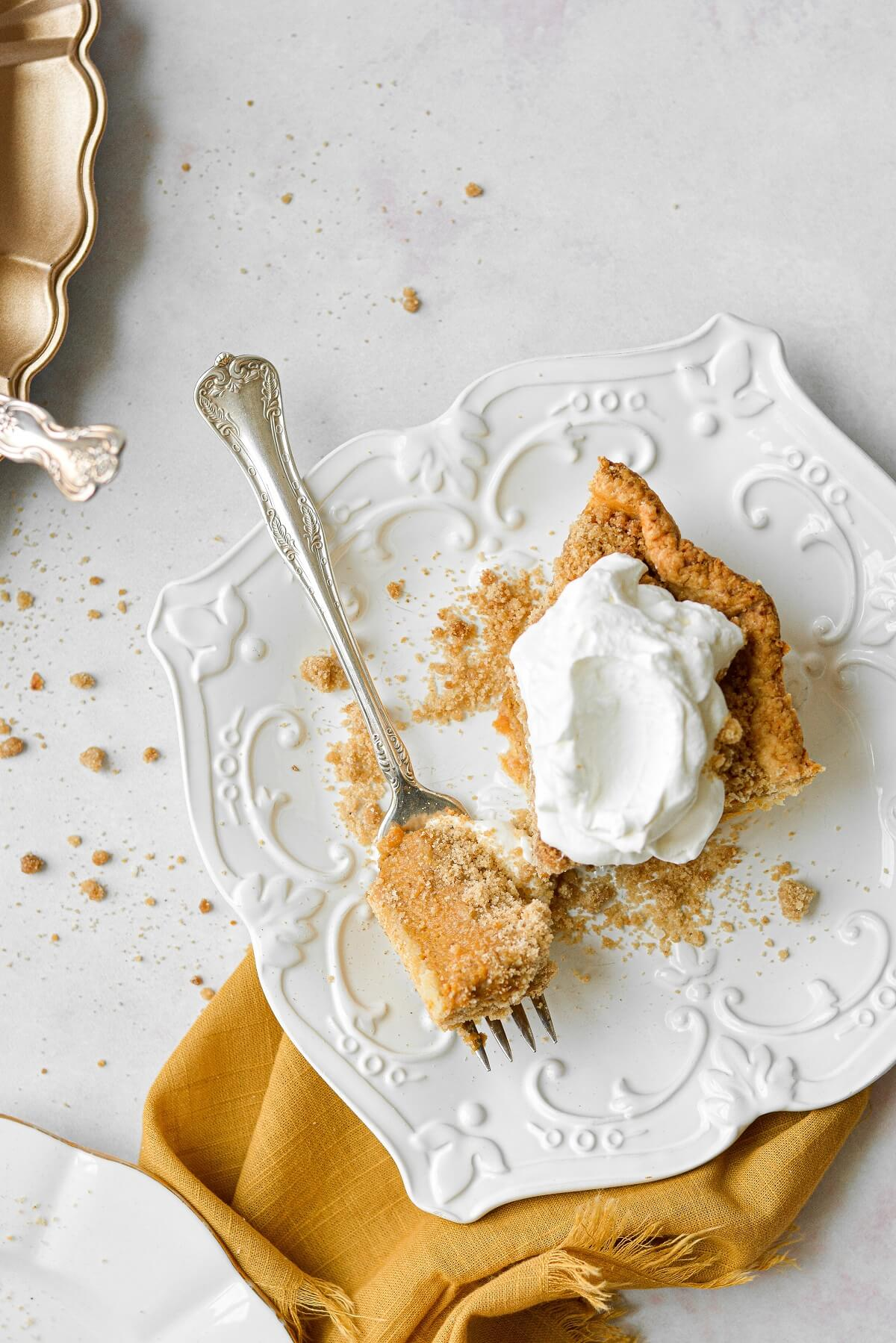 A slice of pumpkin crumb pie on a white plate, topped with whipped cream, with a yellow linen napkin tucked under the plate.