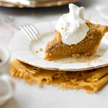 A slice of pumpkin bourbon crumble pie on a white plate, topped with whipped cream, with a yellow linen napkin tucked under the plate.