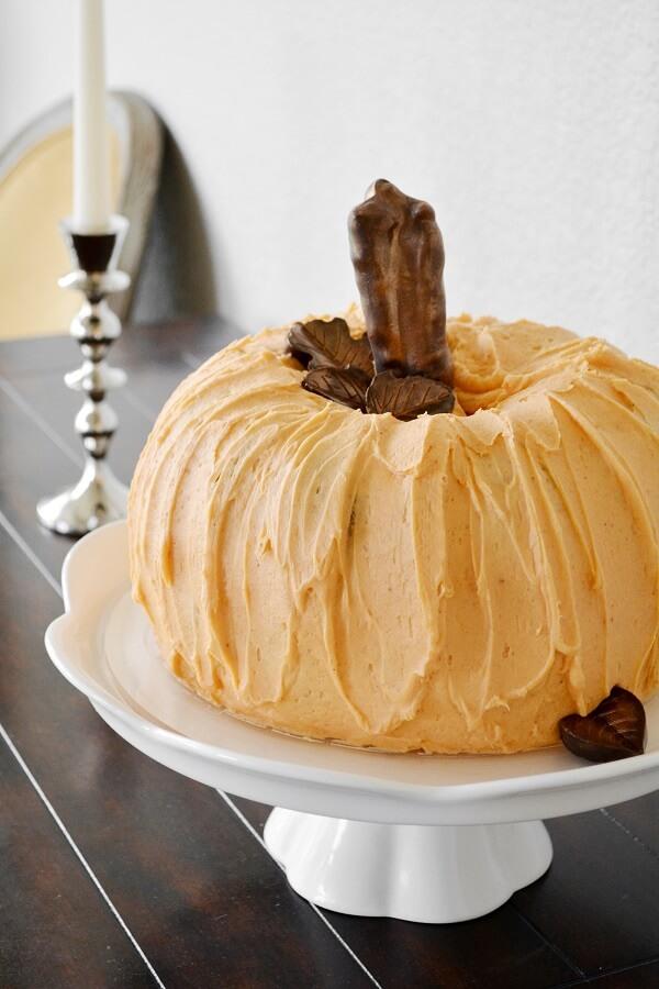 A cake shaped like a pumpkin, with orange buttercream, chocolate leaves and a chocolate stem, on a white cake stand.