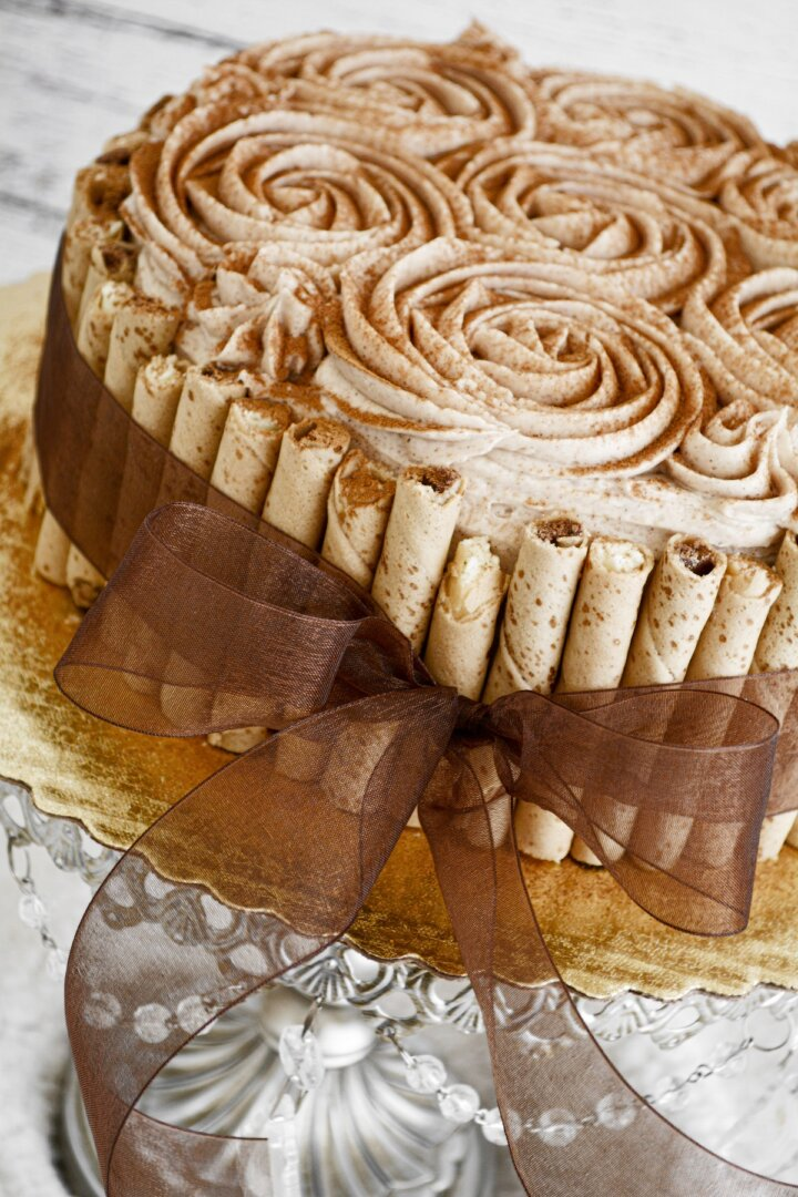 Snickerdoodle cake with buttercream rosettes, pirouette cookies around the cake, tied with a brown ribbon.
