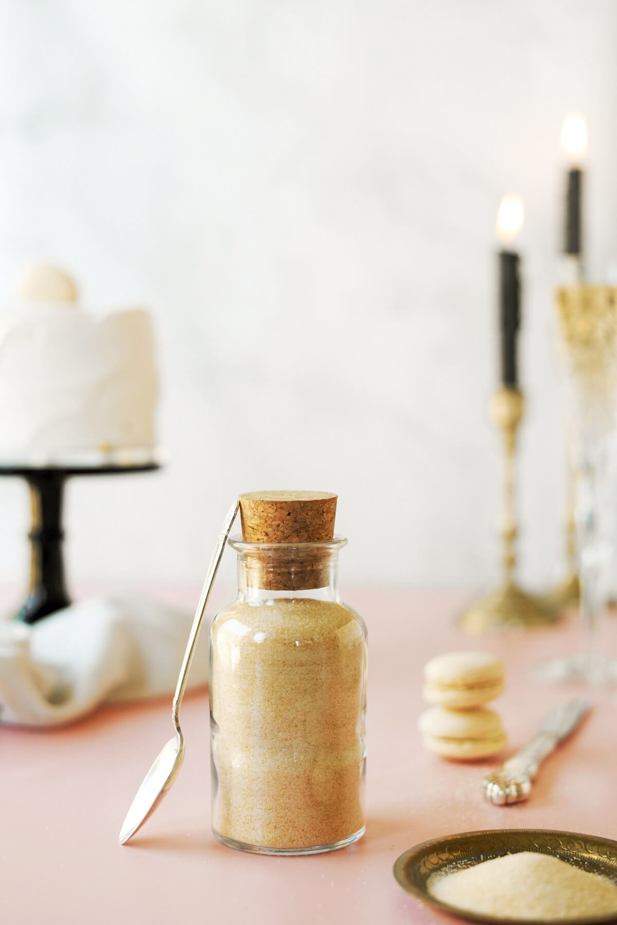 A glass jar filled with toasted sugar, with a cake, candles and macarons in the background.