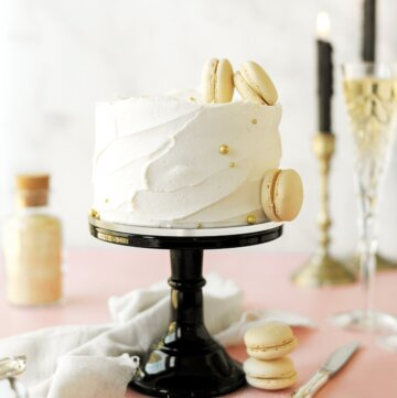 Toasted sugar champagne cake on a black cake stand, with candles, macarons and glasses of champagne.