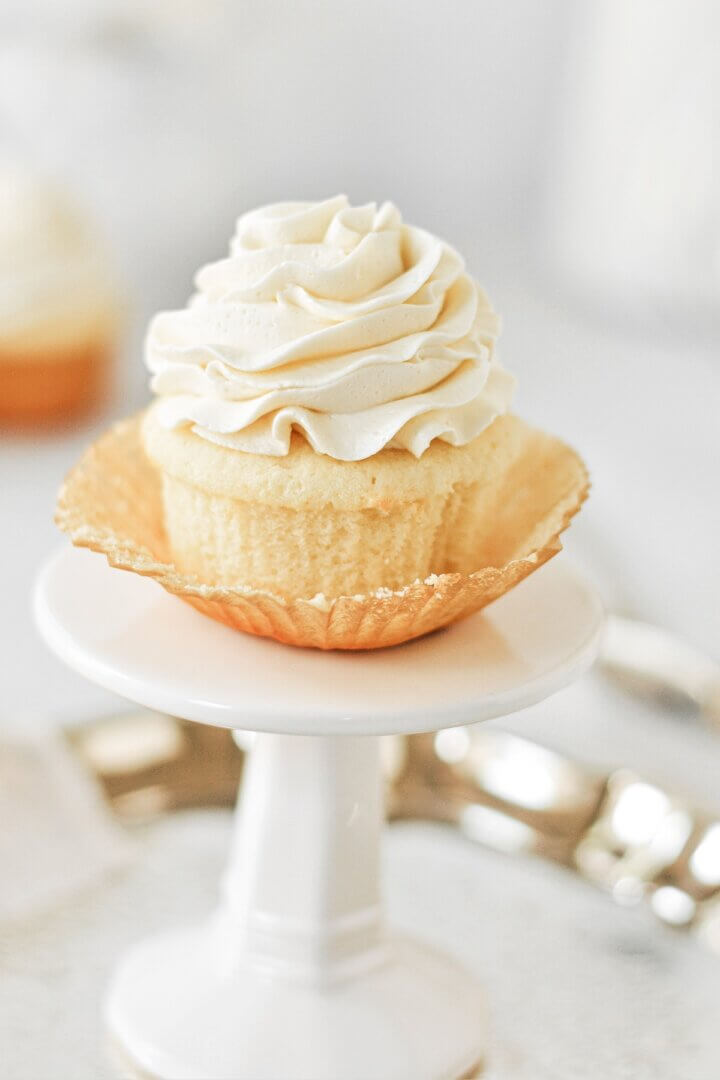 A vanilla cupcake with the wrapper pulled open.