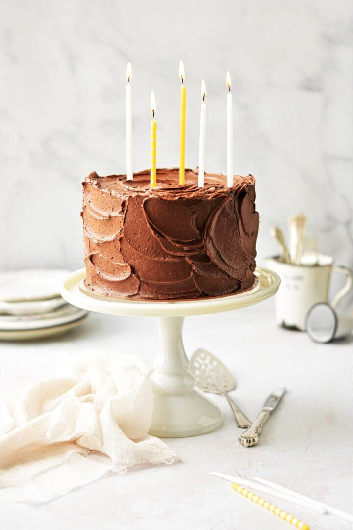 A chocolate frosted yellow layer cake on a white cake stand, topped with yellow and white birthday candles.