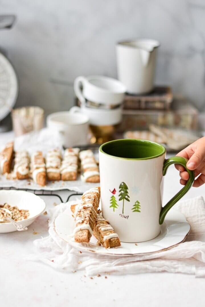 Butter pecan biscotti next to a Christmas mug.