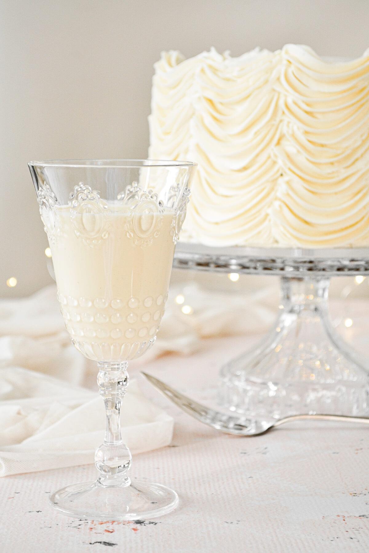 A glass of eggnog with a cardamom cake with eggnog buttercream.