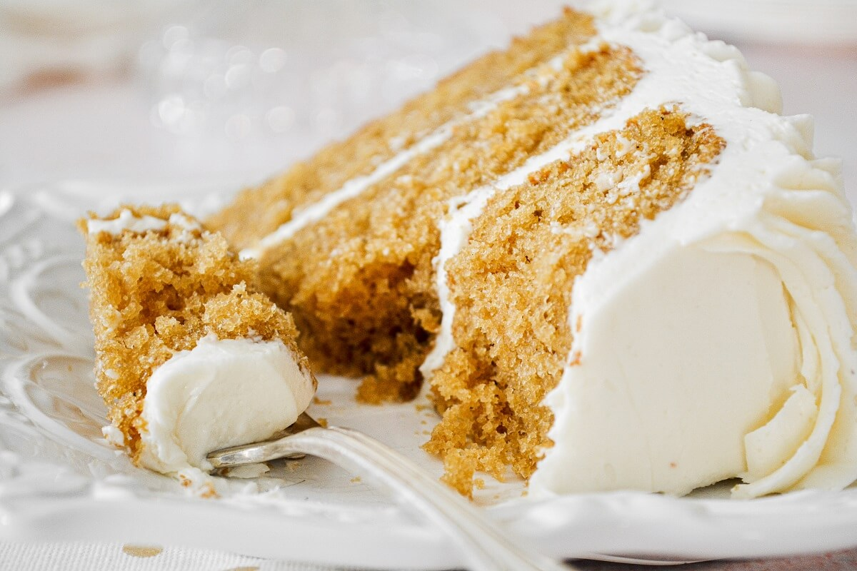 A slice of cardamom cake with eggnog buttercream, with a bite taken.