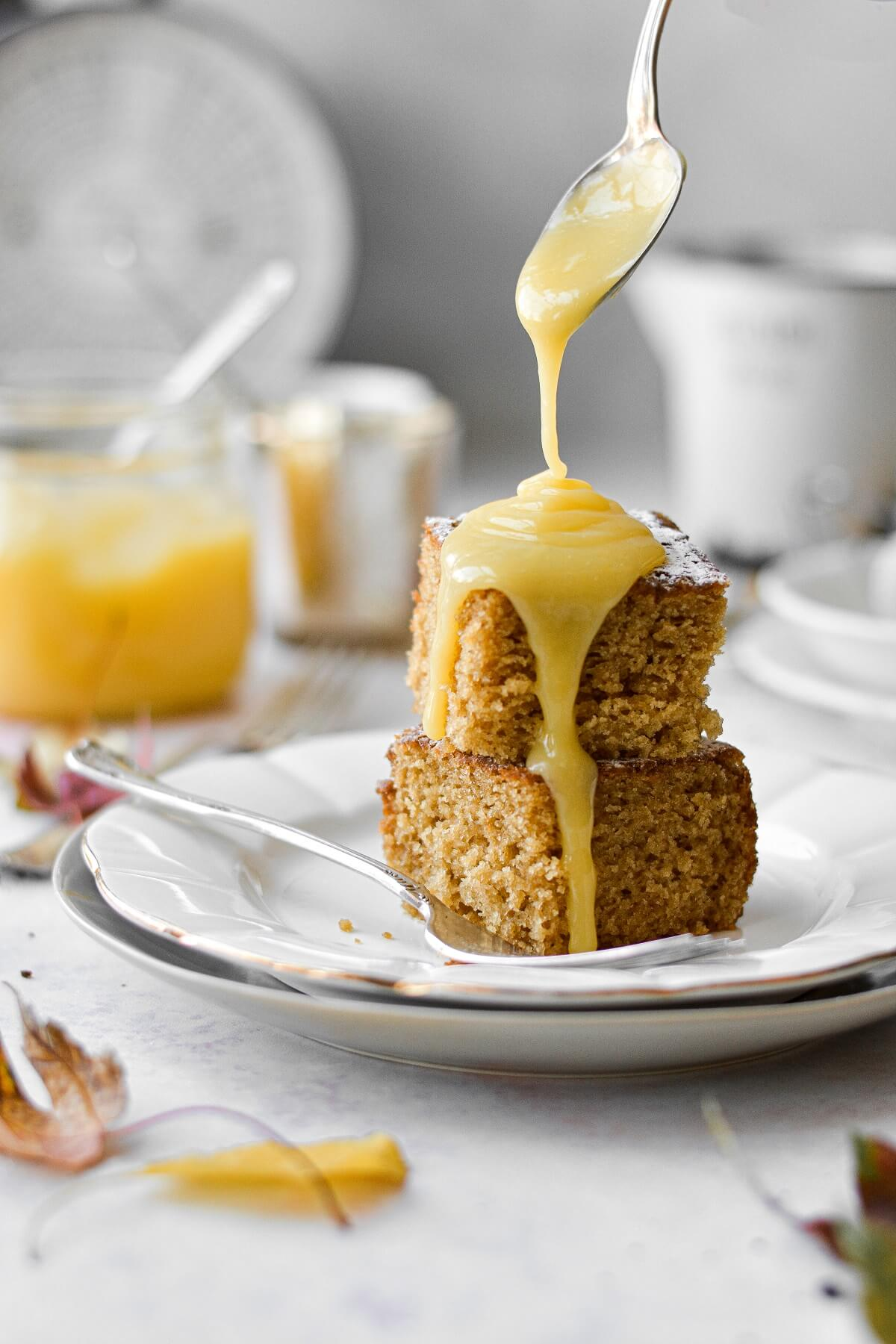 Lemon curd poured over pieces of cardamom ginger cake.