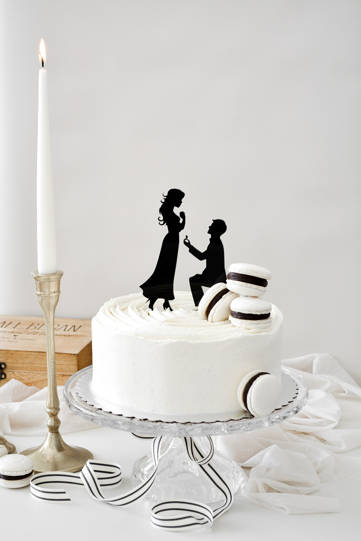 Cake on a crystal cake stand, with French macarons on top.