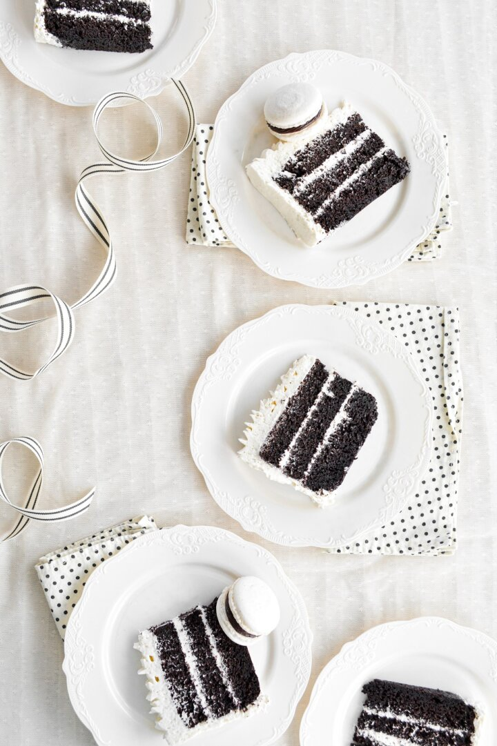 Five pieces of chocolate cake with vanilla buttercream, on white plates.