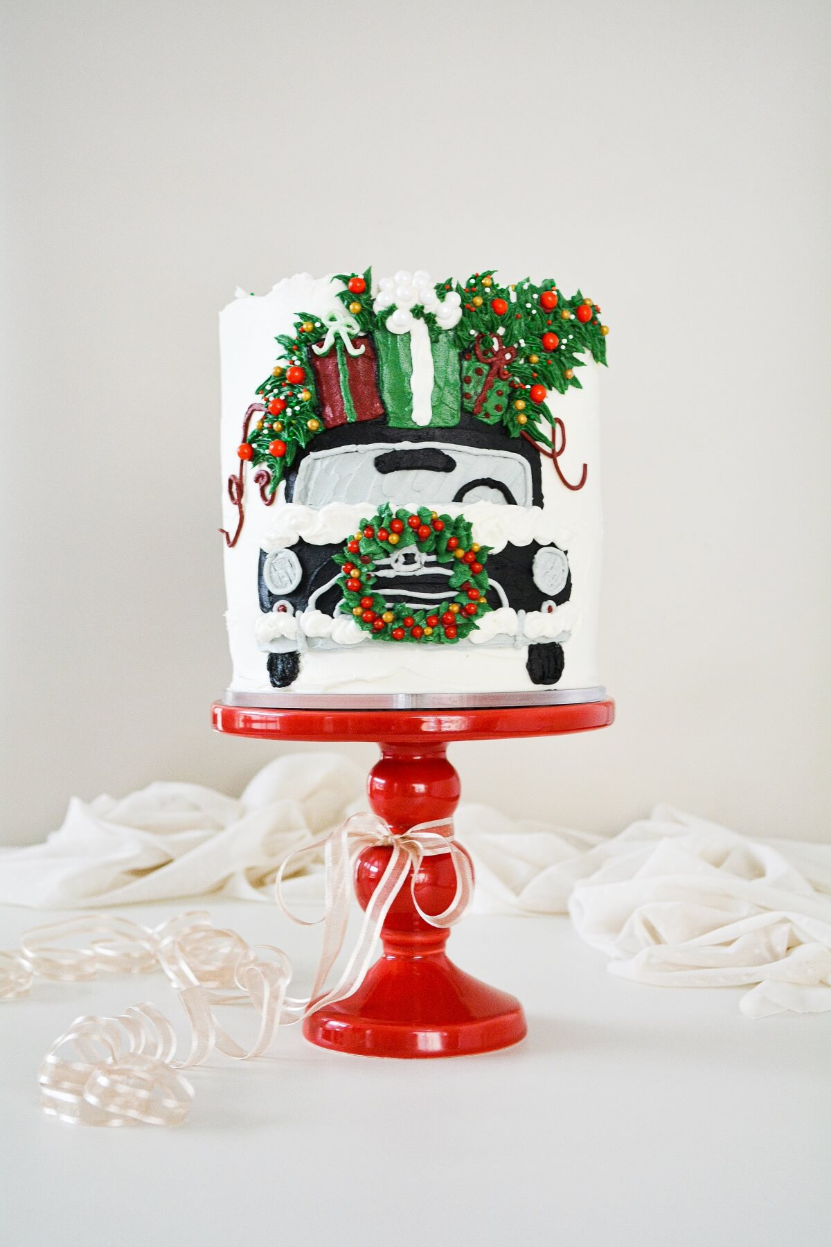 A Christmas cake decorated with a car and presents painted in buttercream.