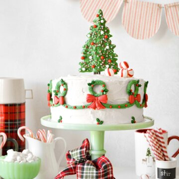 A Christmas cake with a candy tree topper with sprinkles, peppermints and buttercream wreaths piped around the sides.