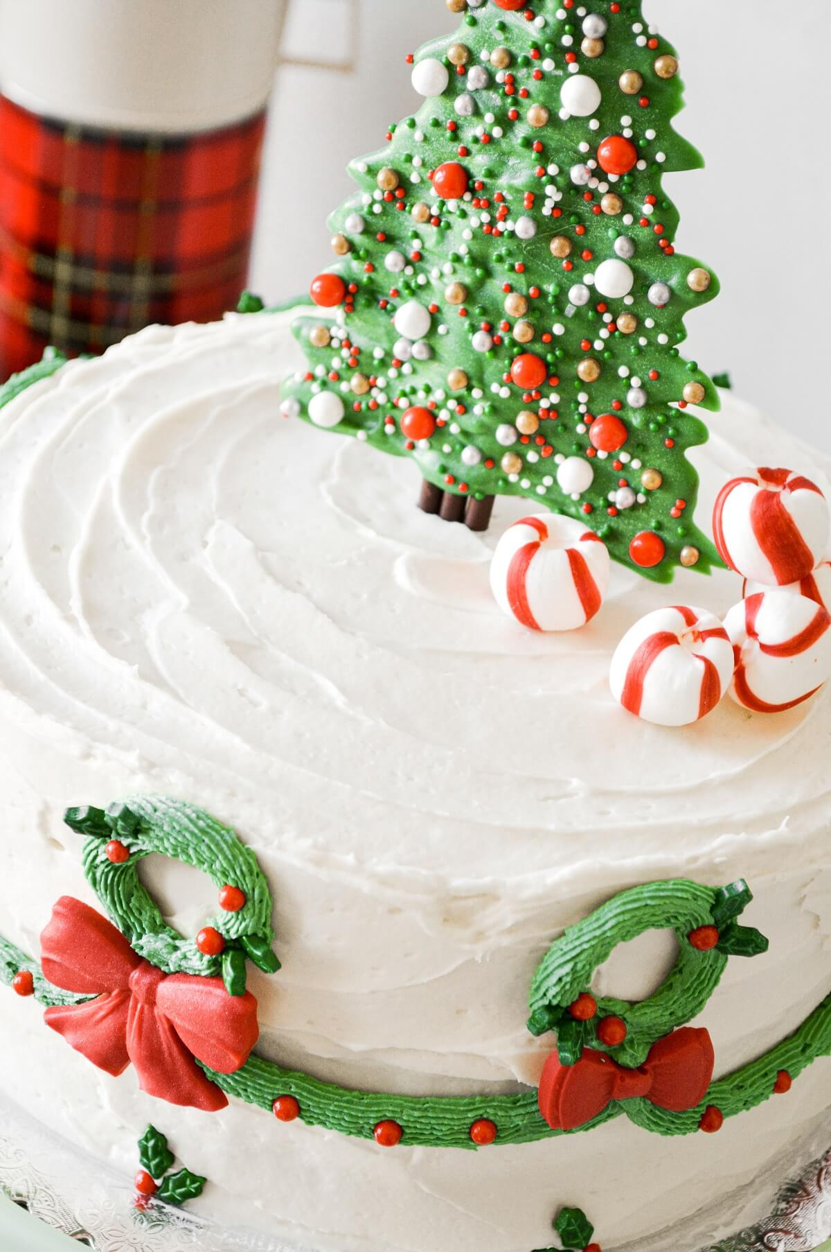 A Christmas cake with a candy Christmas tree cake topper with sprinkles, peppermints and buttercream wreaths piped around the sides.