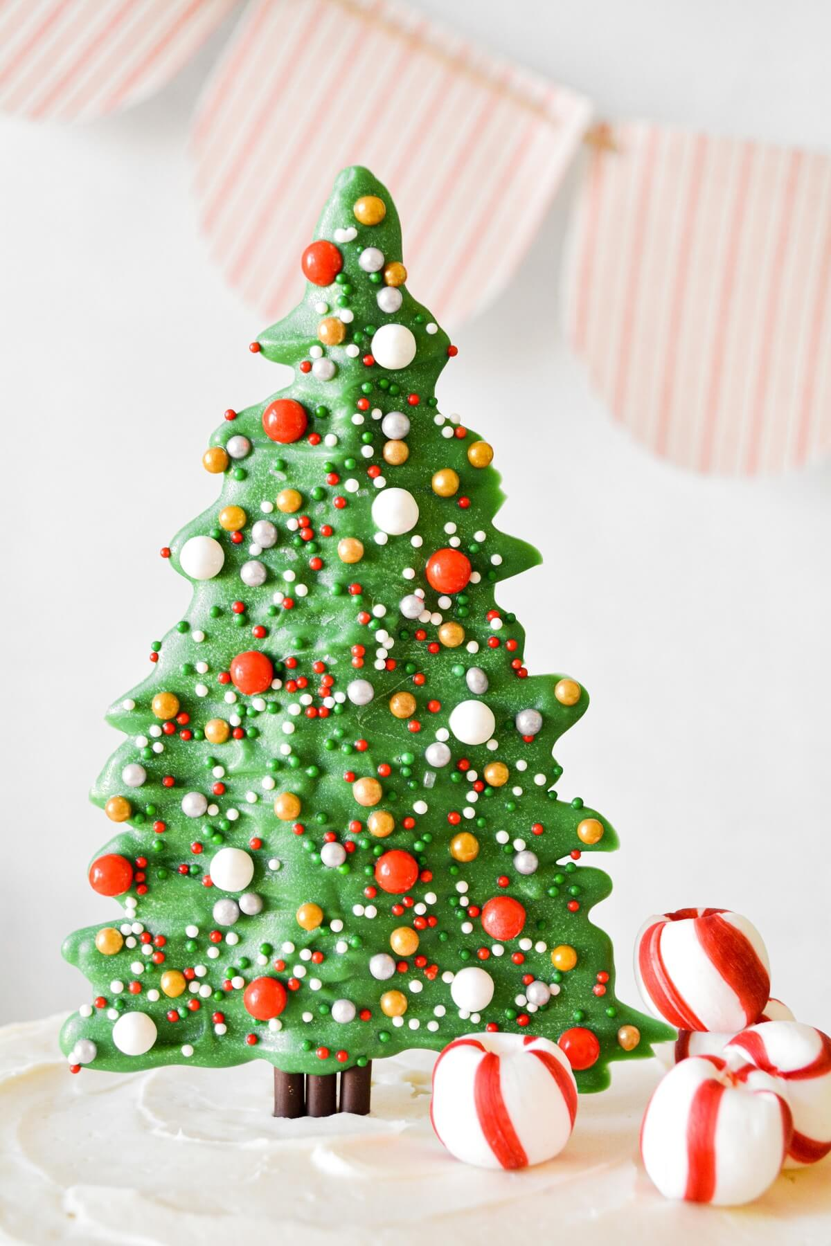 Candy Christmas tree cake topper with sprinkles, on top of a cake.