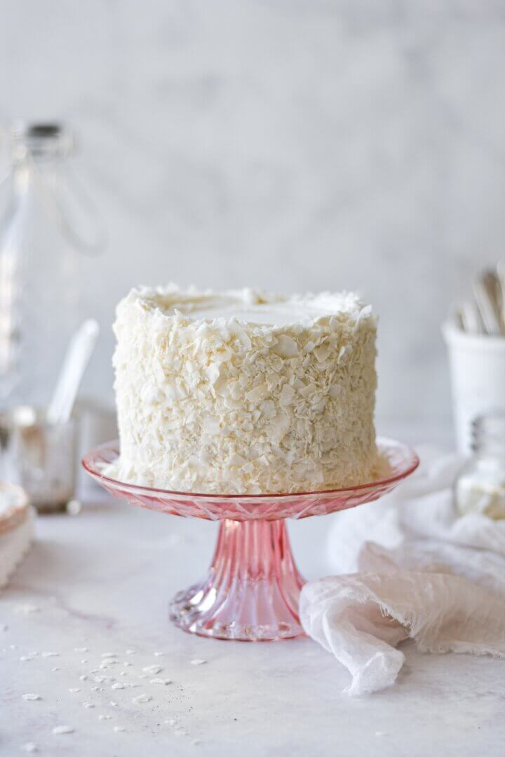 Coconut cake on a pink cake stand.