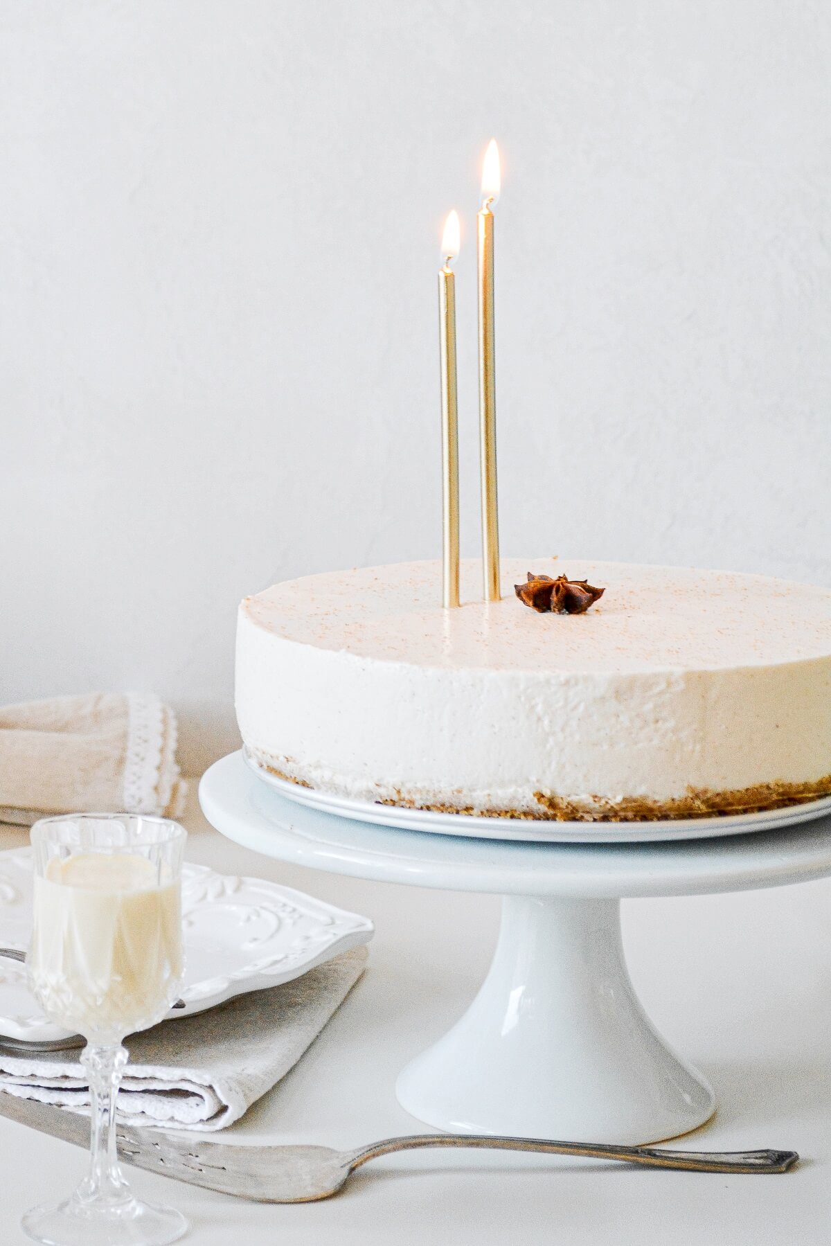Eggnog cheesecake with two gold candles.