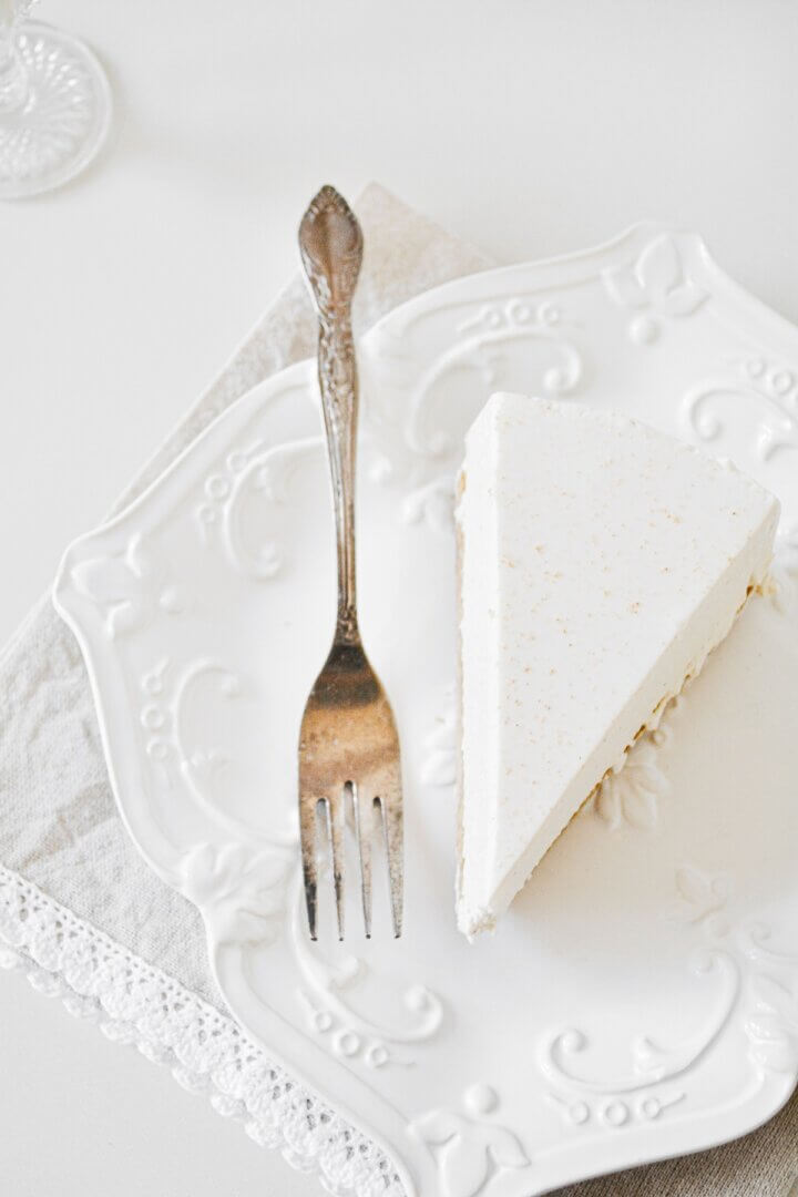 A piece of eggnog cheesecake on a white plate.