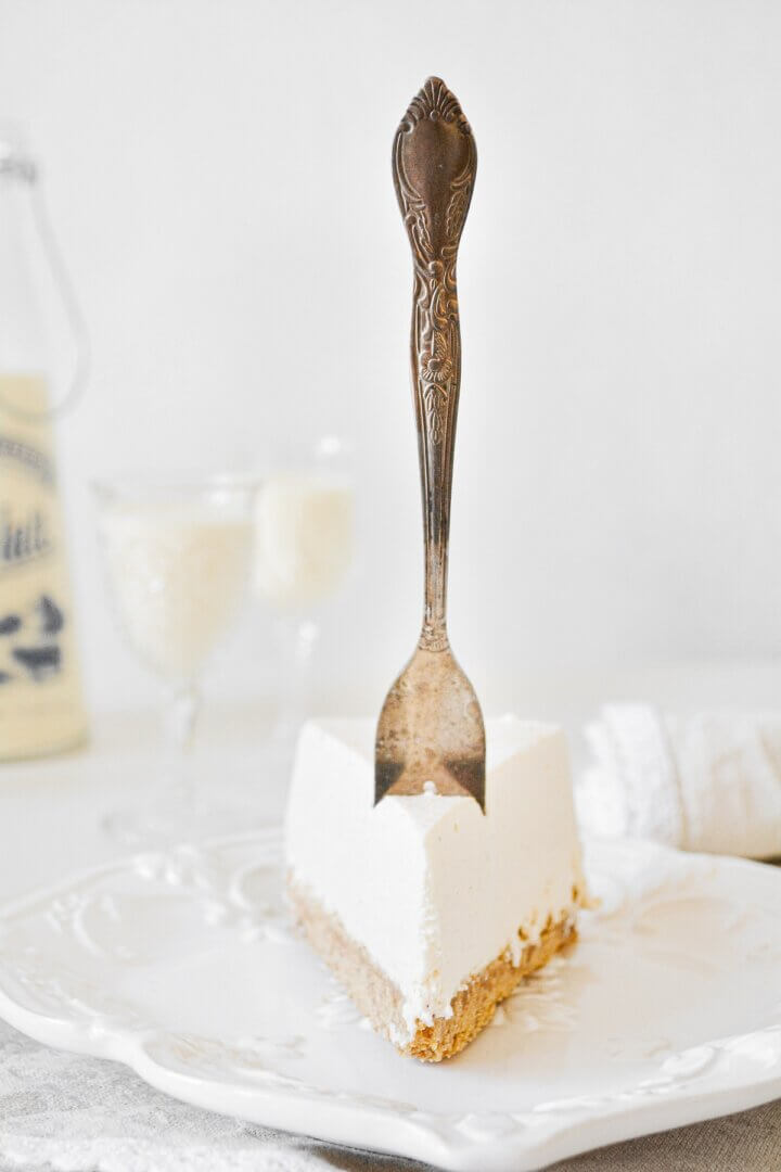 A piece of eggnog cheesecake with a vintage fork stick in the top.