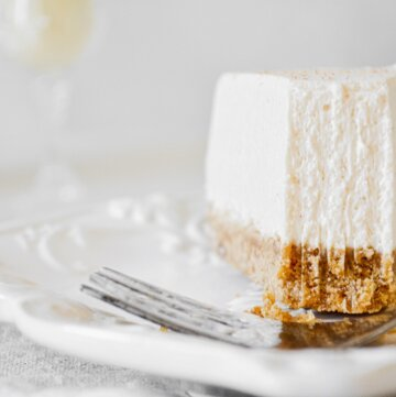 A piece of eggnog cheesecake with a bite taken.