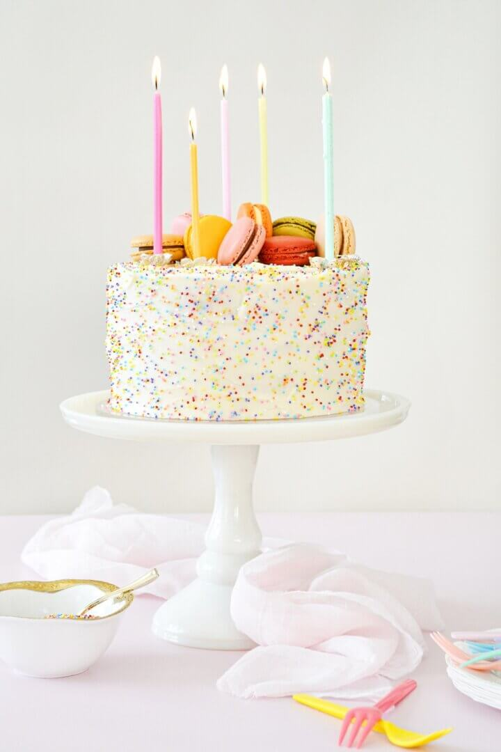 Funfetti cake on a white cake stand, covered in sprinkles, and topped with colorful macarons and birthday candles.