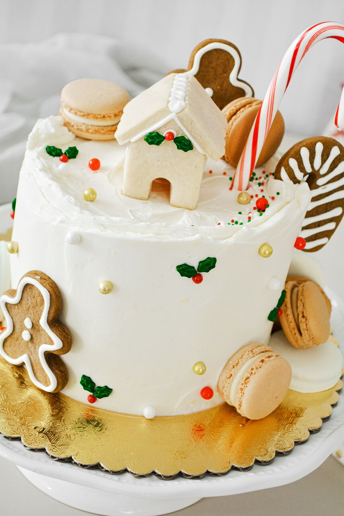 A Christmas cake decorated with candy canes and Christmas cookies.