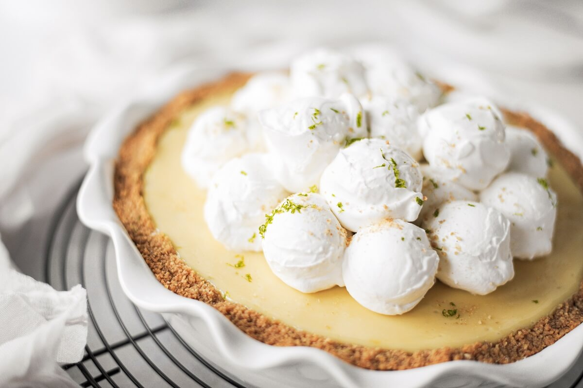 A key lime pie with scoops of whipped cream.