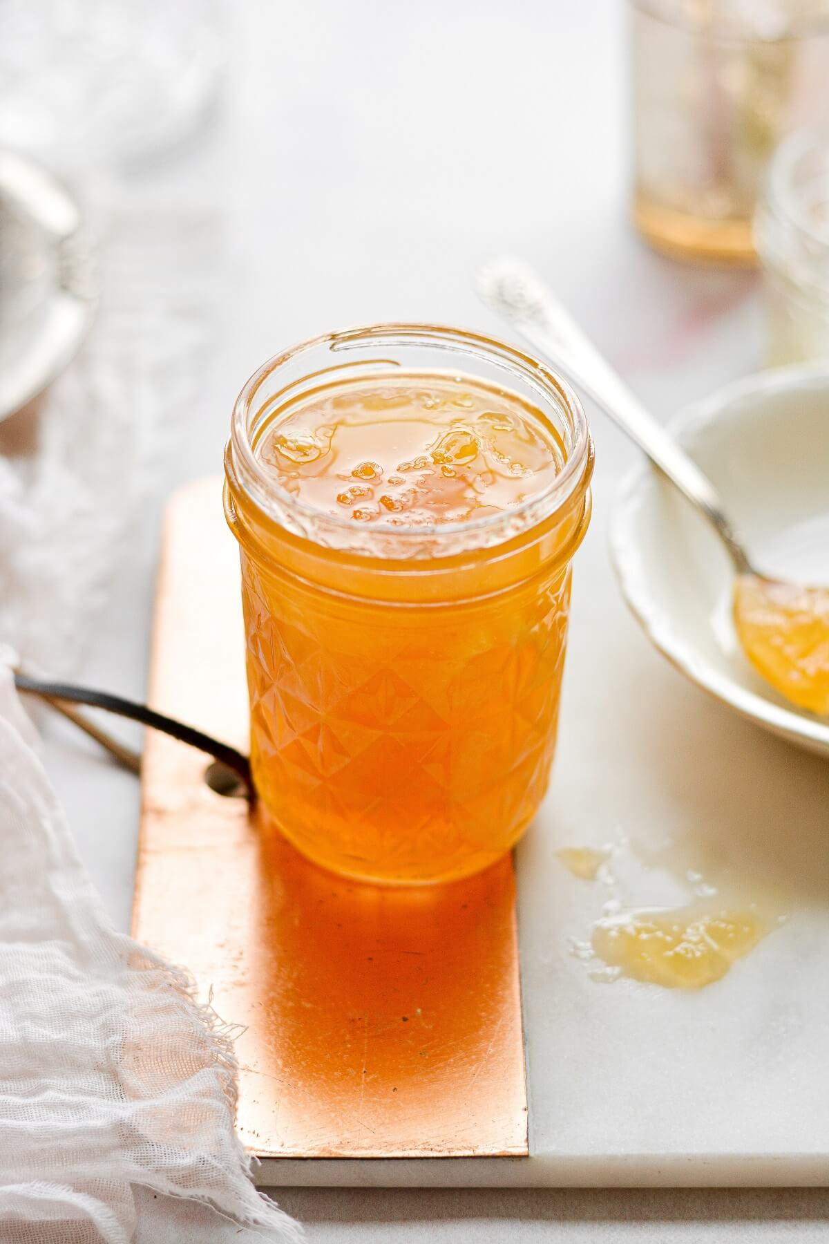 A jar of lemon marmalade with a silver spoon.